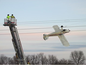 Small airplane suspended from electrical wires south of Shakopee